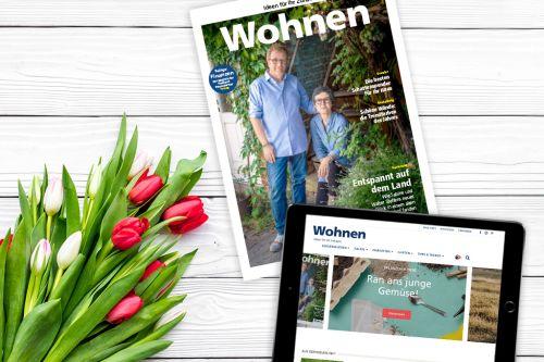 Ein Magazin, ein iPad und Blumen auf einem Tisch.