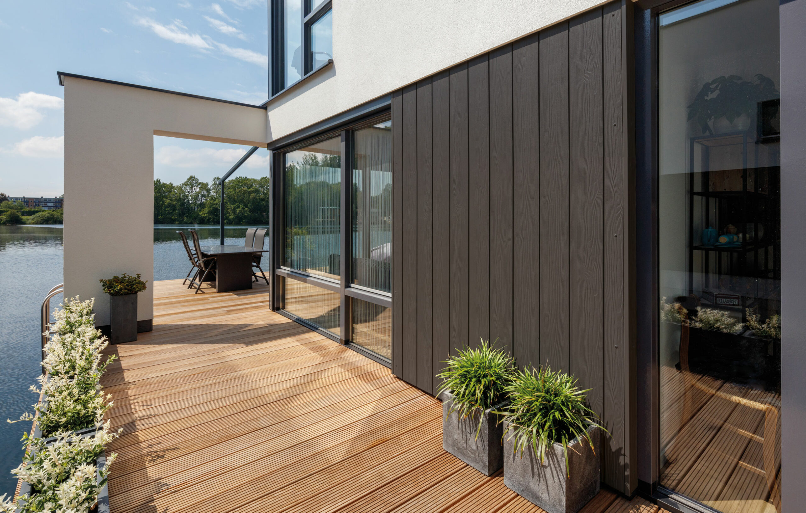 Cedral Terrassen und Profilschalung Keyvisual mit Gebäude am See.