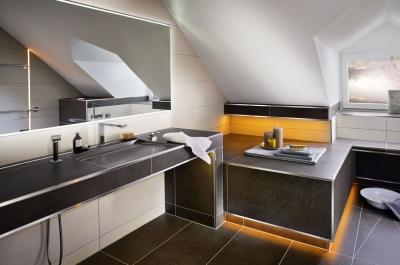 Schlüter-Systems® Keyvisual zur Badgestaltung mit einem schwarzgefliesten Bad und orangener Beleuchtung mit Schlüter LIPROTEC.