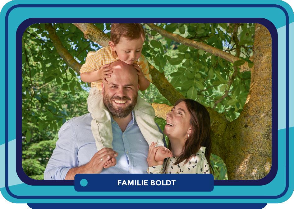 TV-Monitor mit Familie Boldt vor einem Baum mit grünen Blättern. Ein Mann, eine Frau und ein kleiner Junge auf den Schultern des Mannes.