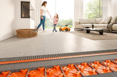 Wohnzimmer mit Frau und Kind im Hintergrund. Im Fokus steht die Fußbodenheizung von Schlüter-Systems KG anschaulich dargestellt mit einem Blick unter die Fliesen.
