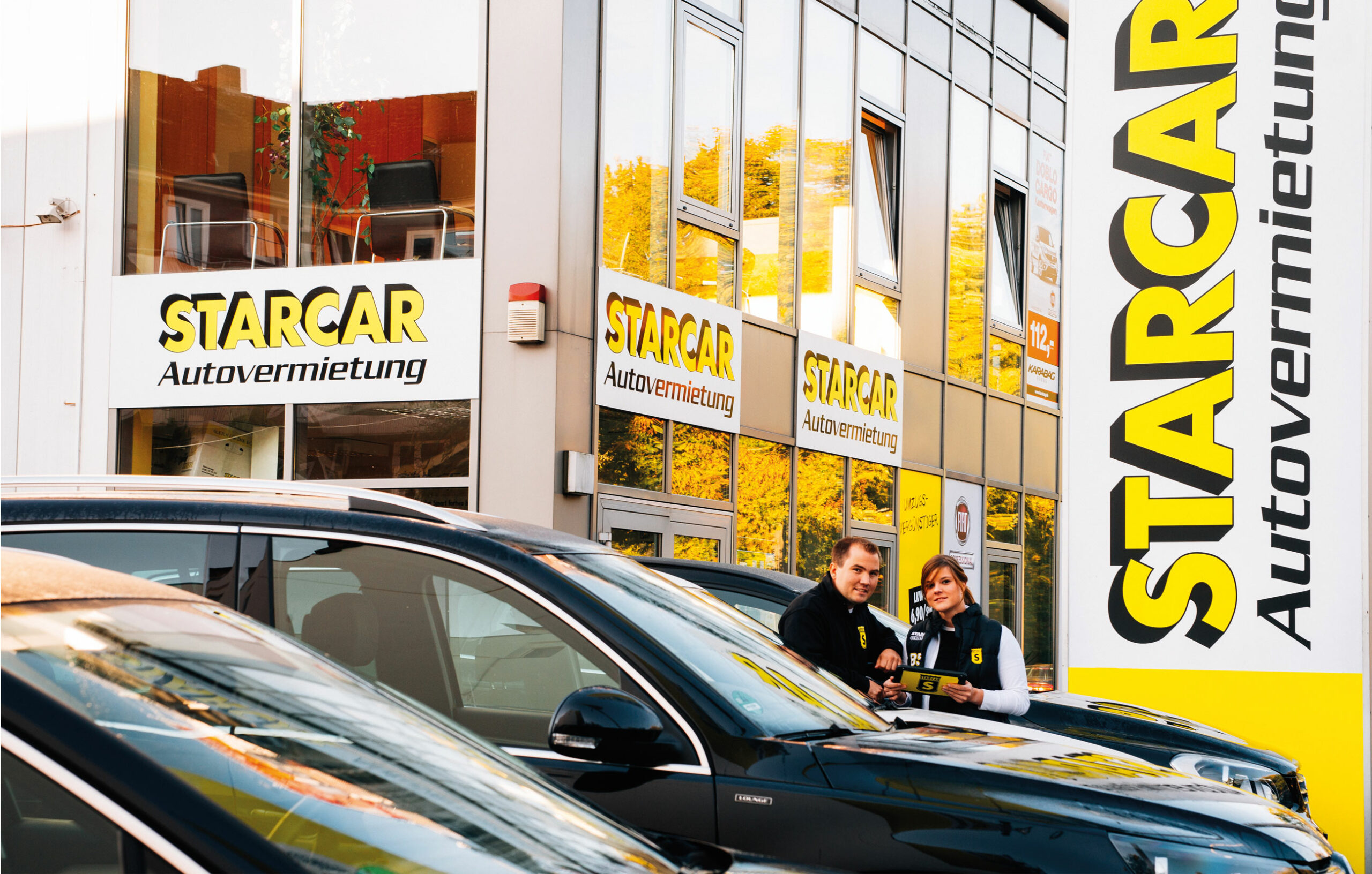 STARCAR Keyvisual. Zwei Mitarbeiter von Starcar vor einem Autovermietungsgebäude von STARCAR mit Fahrzeugen.